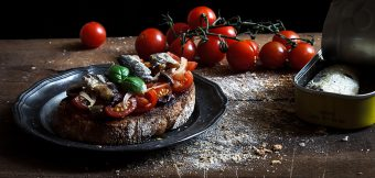 bruschetta con sardine, pomodorini, olive e cipolla