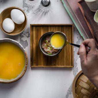 Condite i gamberetti con un pizzico di sale, pepe e aglio in polvere.<br /> Suddivideteli in due ciotoline. <br /> Aggiungete i cipollotti e versate sopra il composto di uova.